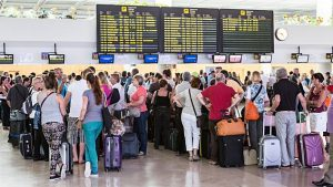 People waiting in line to check in at airport, Lanzarote, Canary Islands, Spain